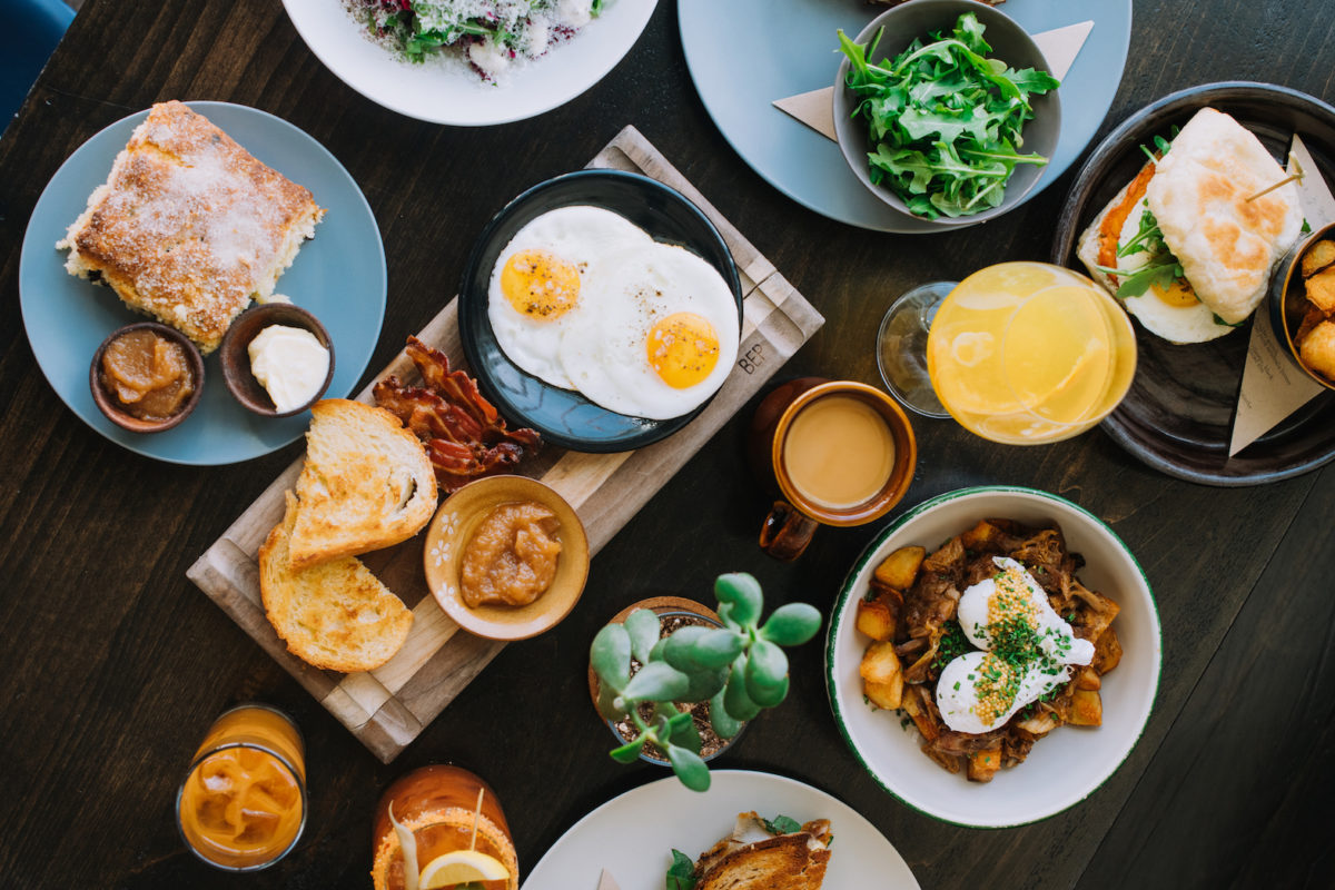 a spread of brunch foods, including eggs, toast, juices, and more.