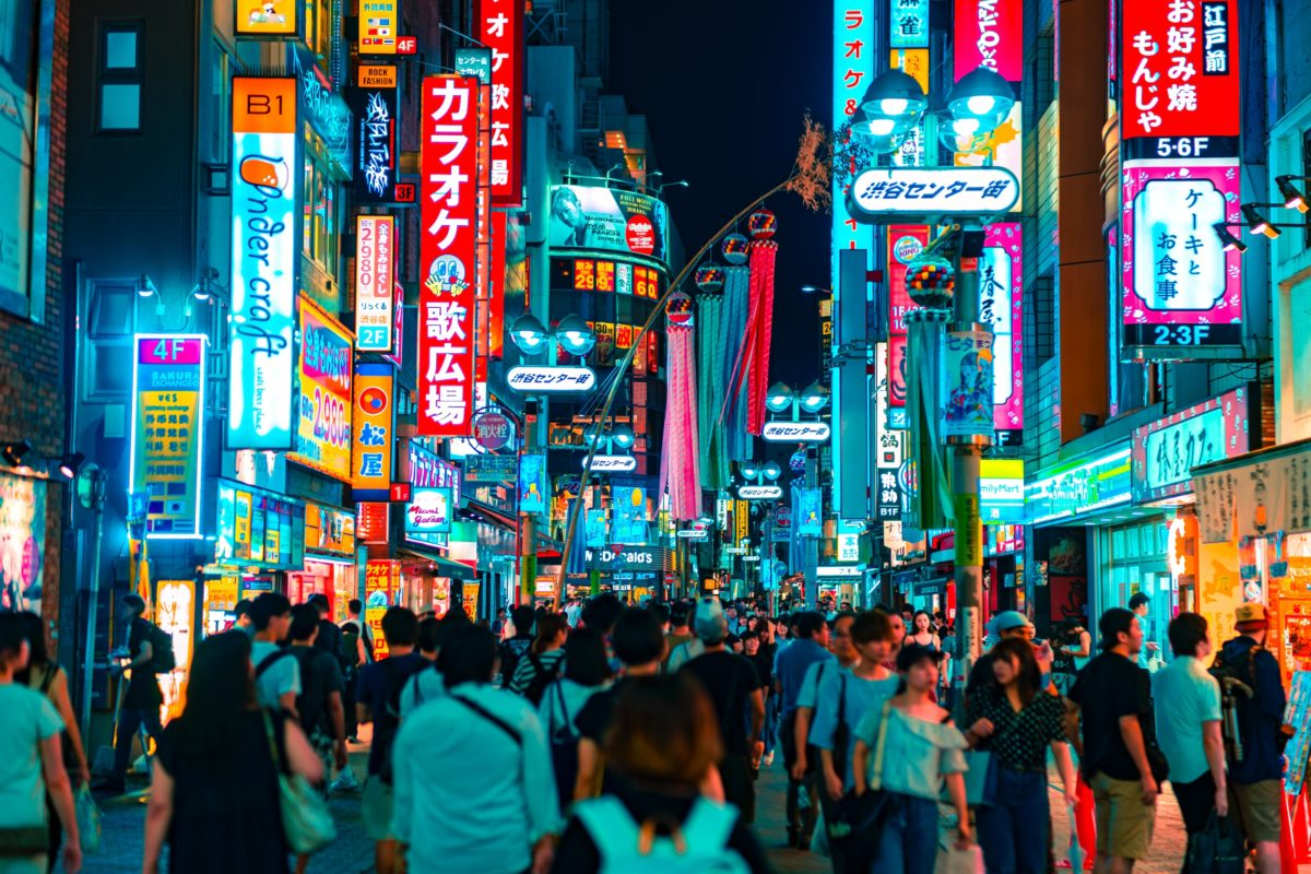 crowds of people walking through Shibuya, a large neighborhood filled with neon signs