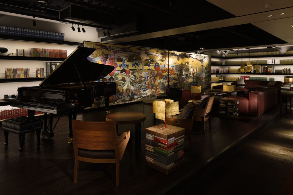 a piano sitting at the front of a dimly-lit room filled with tables, chairs, and books