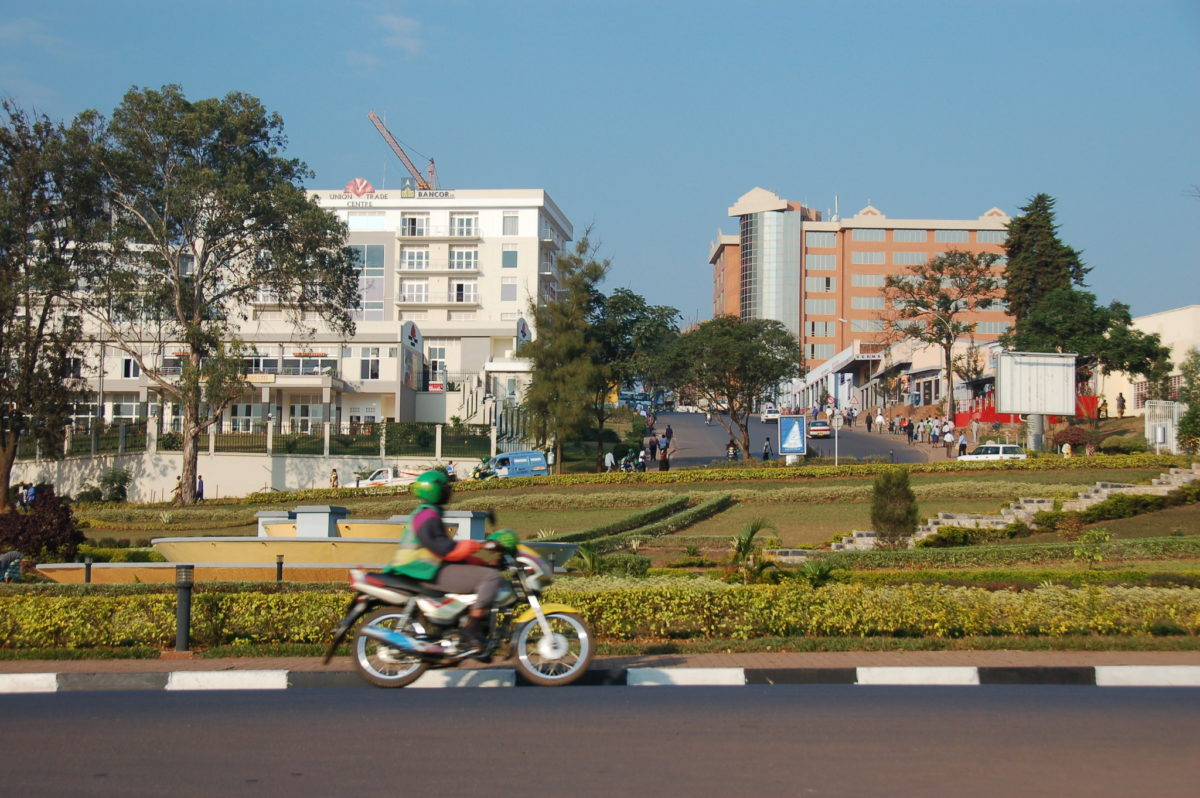 a person riding a motorbike in front of a small park and buildings on a sunny day