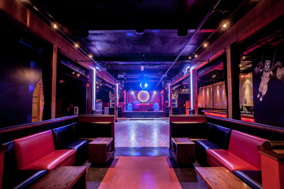 the dark room of a club with a glossy floor and a stage at the end