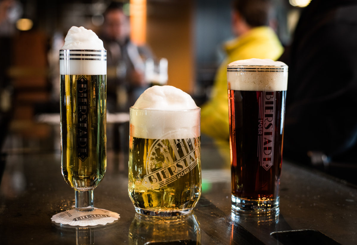 glasses of various sizes with foaming beer