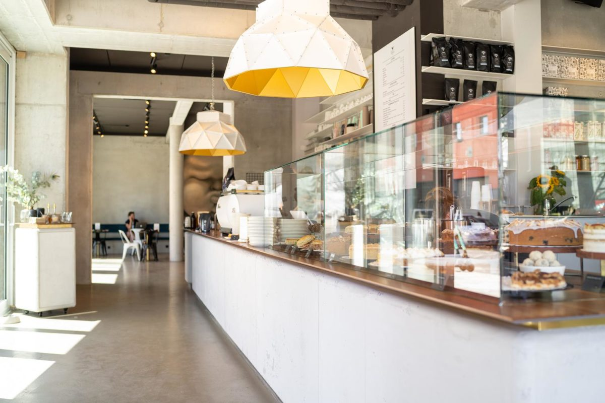 a long counter leading to a dining room inside a brightly lit coffee shop