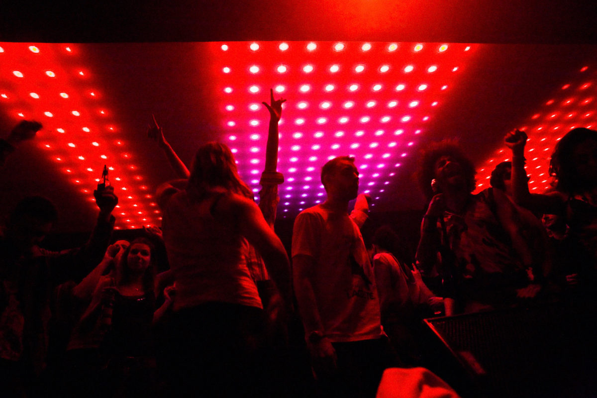 people dancing in a dark nightclub illuminated by red lights