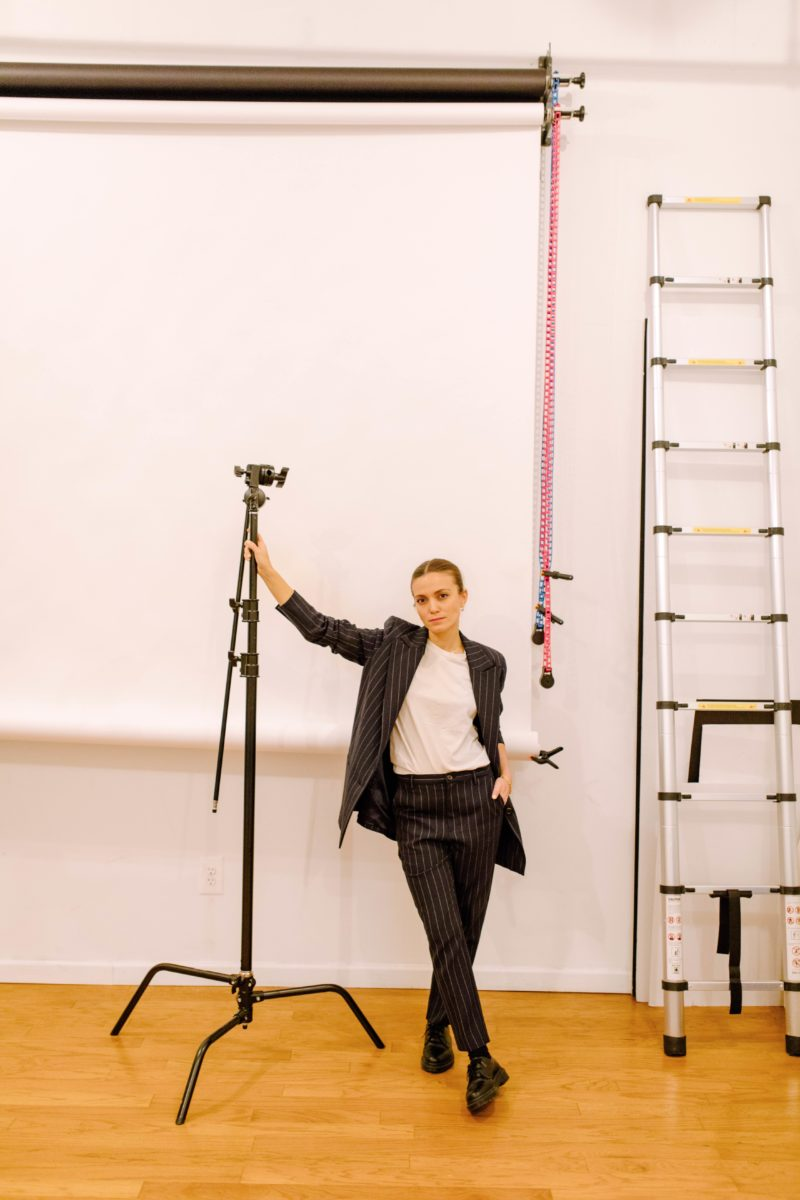 a woman in a suit leans on a lighting tool