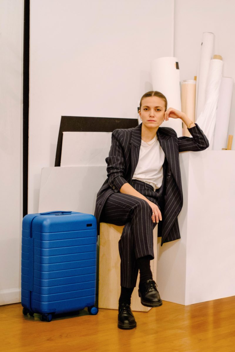 a woman in a suit sits on top of a suitcase