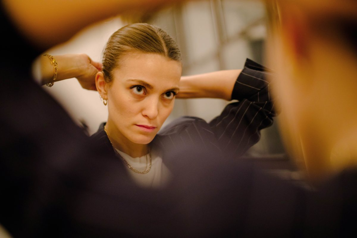 a woman ties her hair in a bun in the mirror