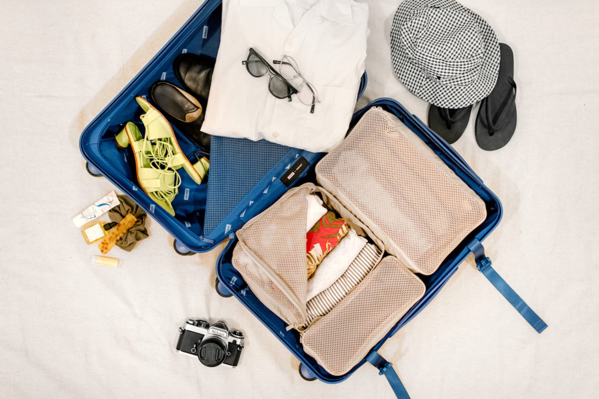 an open suitcase filled with packing cubes, clothes, and accessories