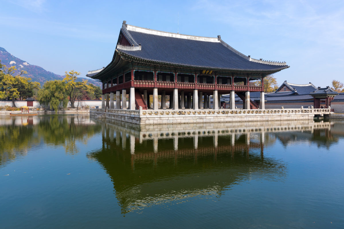 traditional korean palace structure situated over a lake.