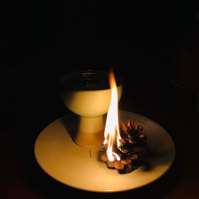 a small fire next to a cocktail in a dark setting