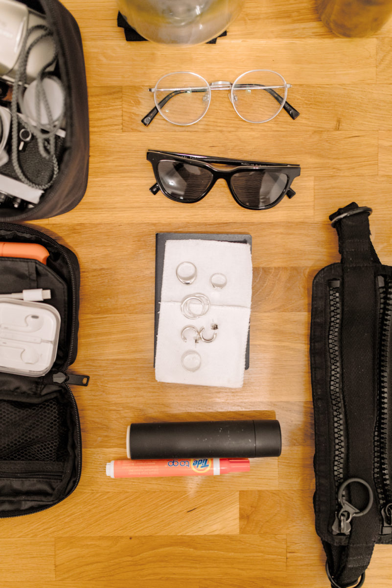 eyeglasses, sunglasses, earrings, rings, and a lint roller on a table