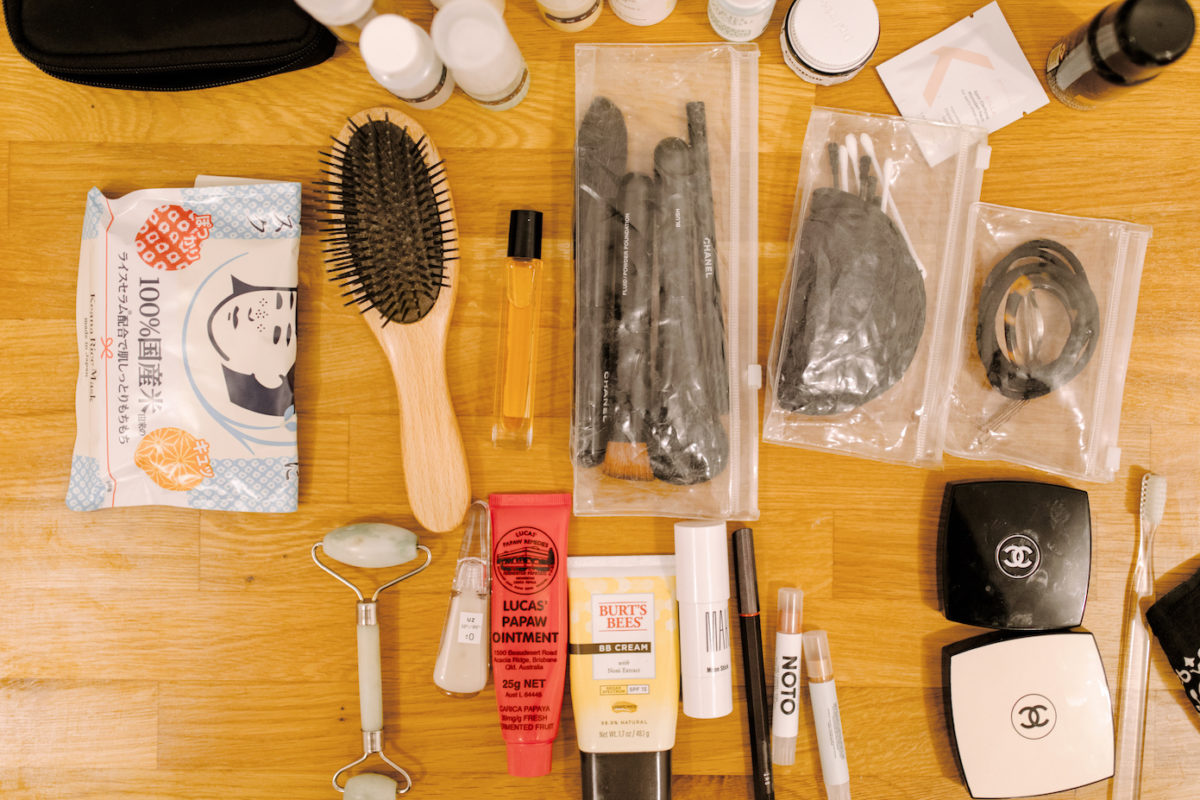 a hairbrush, makeup brushes, makeup, and other toiletries