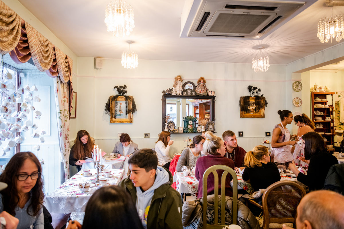 people sitting drinking tea and eating finger foods in a tea room