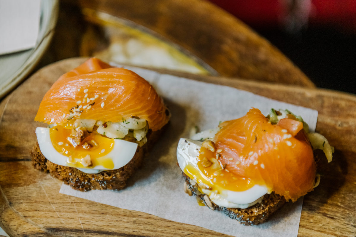 two halves of a bagel topped with egg and lox