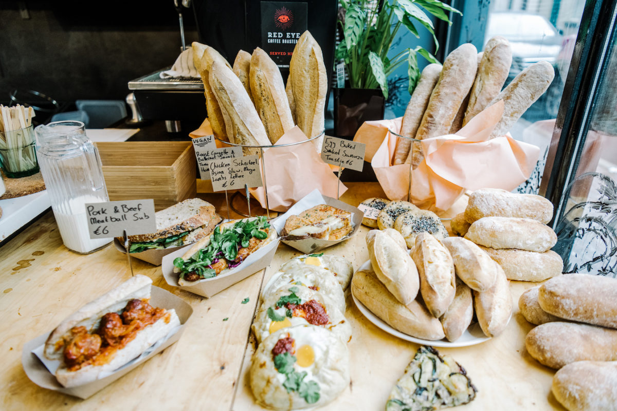 a display of various breads, sandwiches, and pastries topped with egg