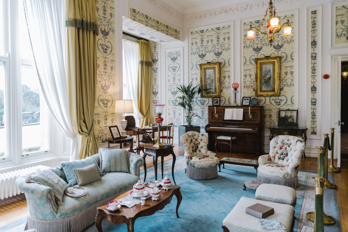 the inside of an elegant drawing room filled with antique furniture, a piano, and a tea set