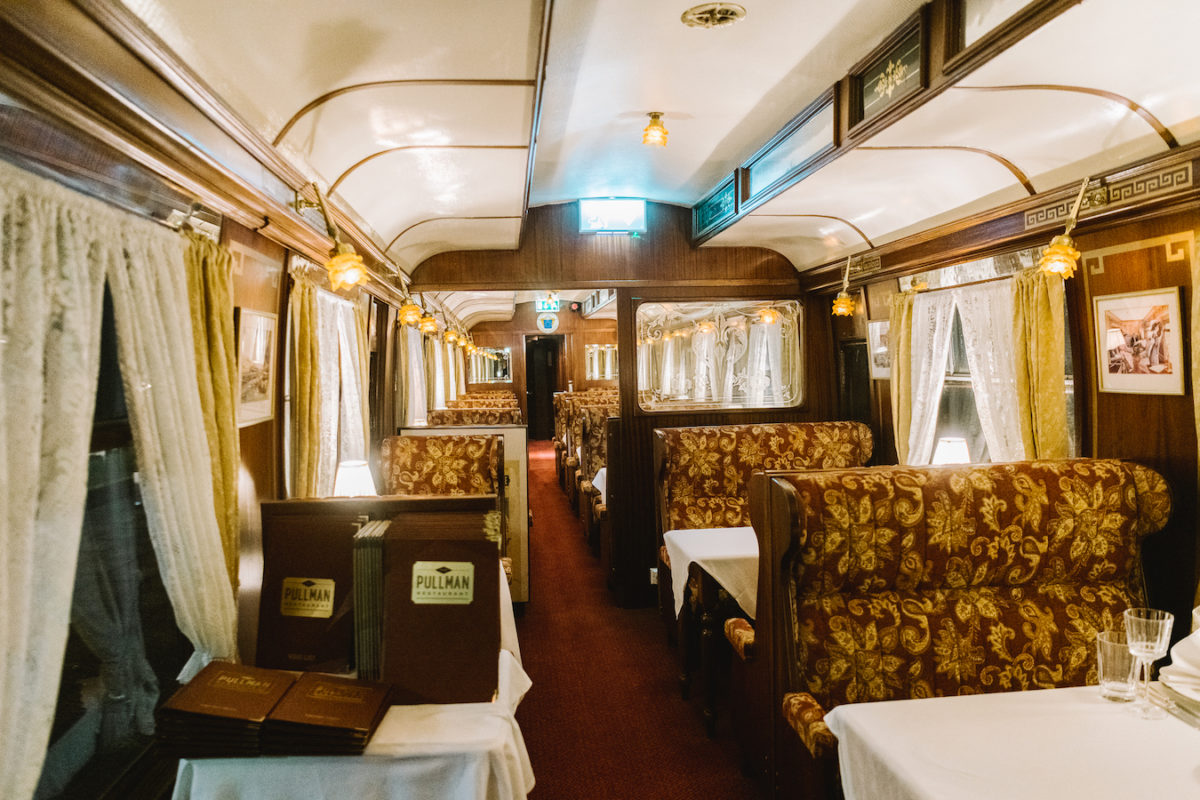 the interior of an antique dining car in a train