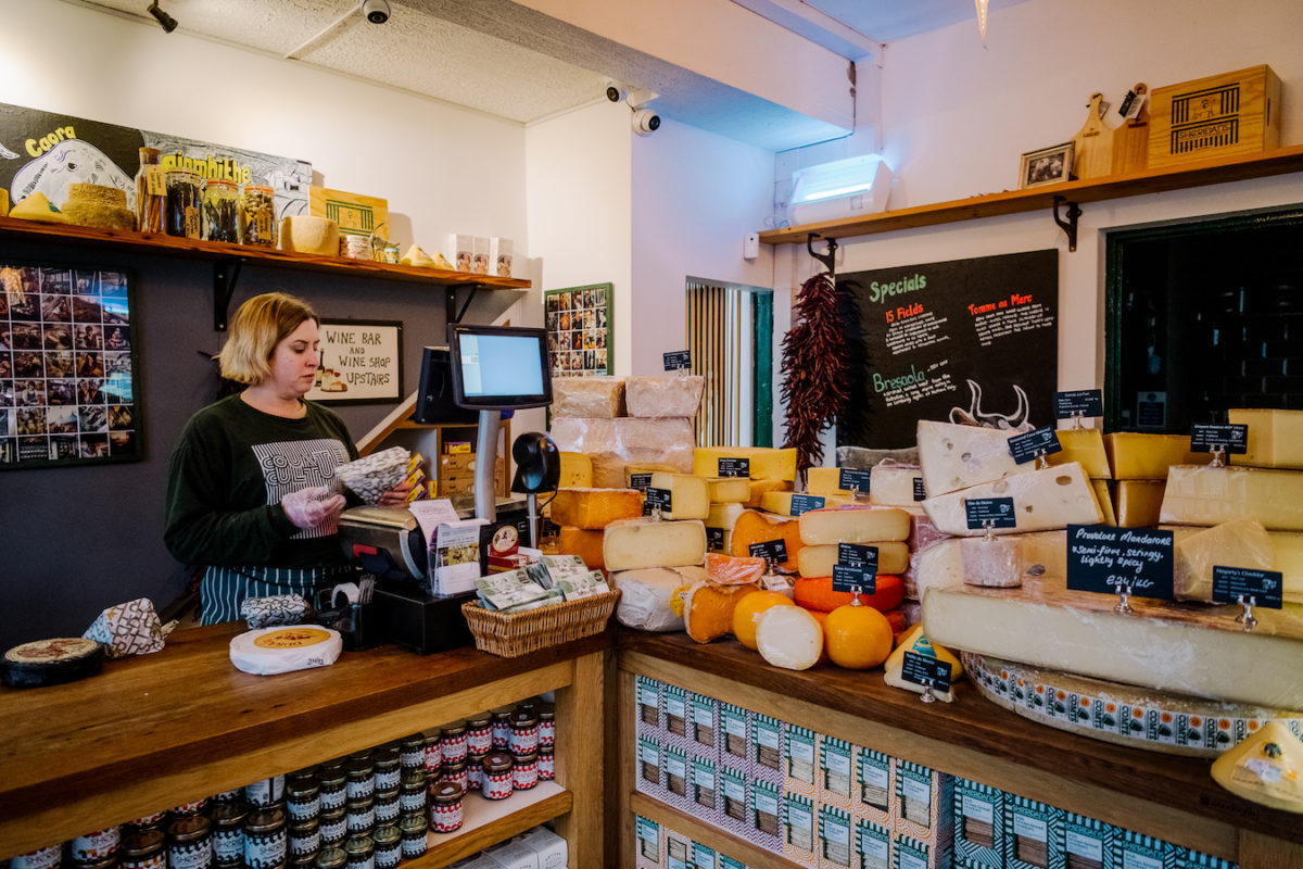 a woman stands at a counter filled with dozens of cheese wheels