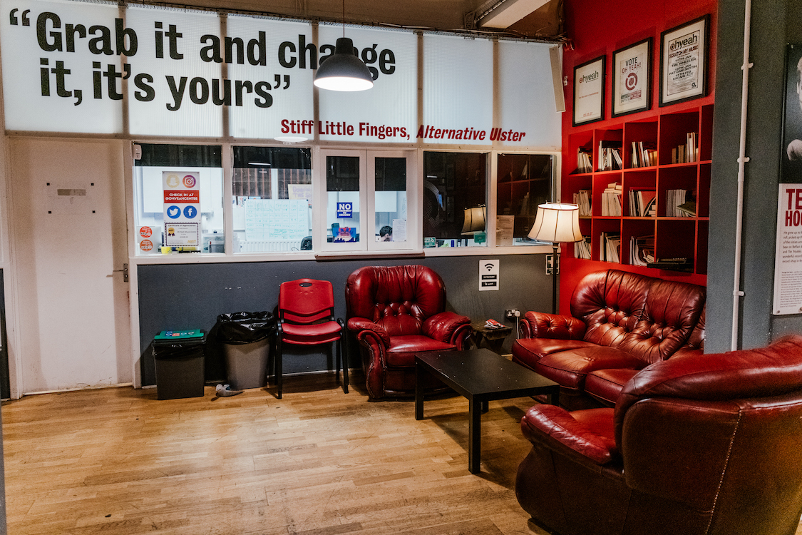 "a room with plush chairs and the quote ""Grab it and change it, and its yours"" on the wall"