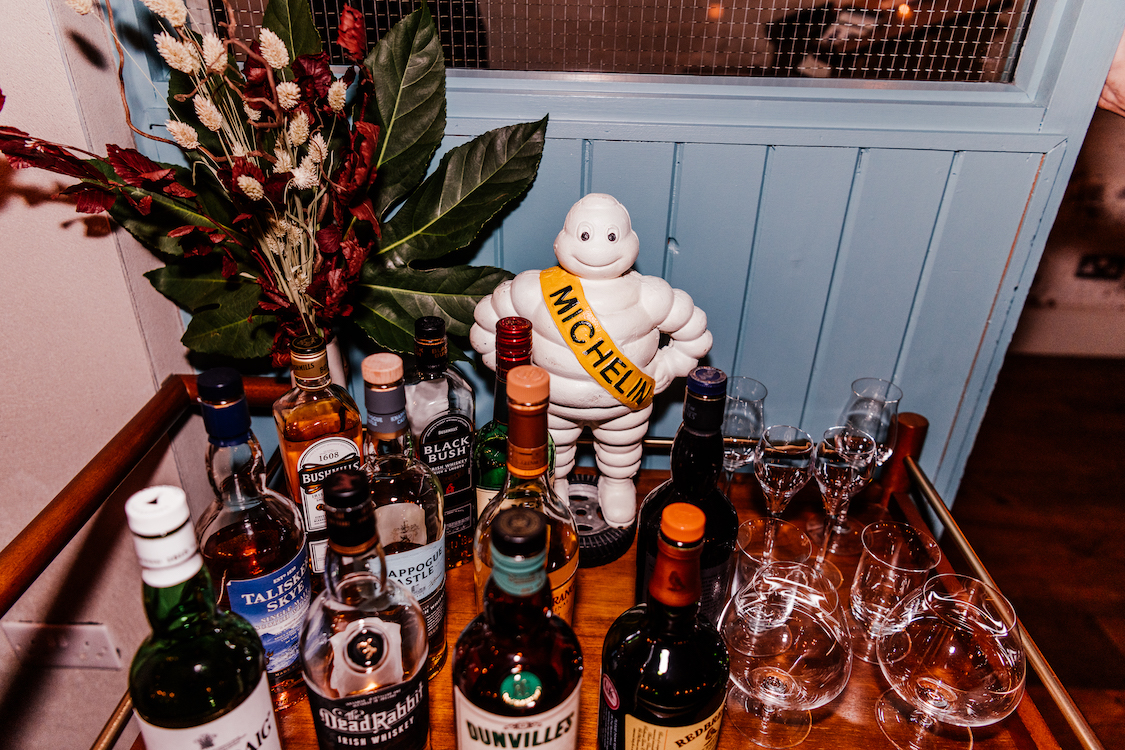 a Michelin man on a tray amongst various bottles of spirits and glasses