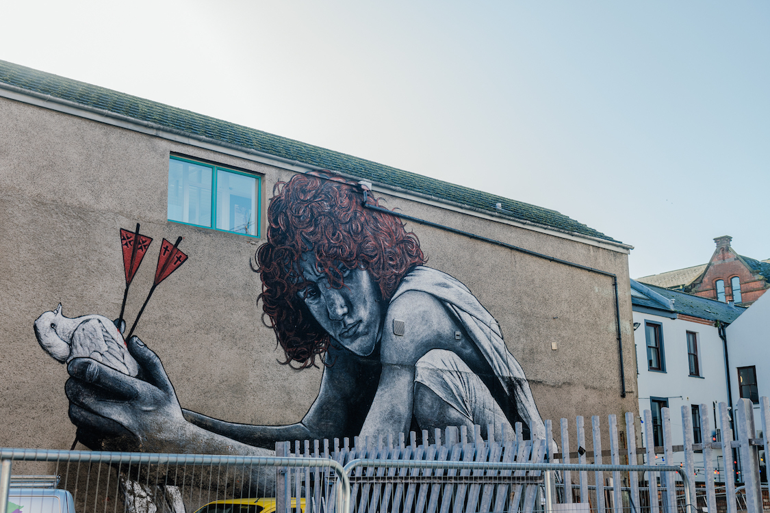 a mural of a person with curly hair crouching while holding a pigeon with two darts in its chest