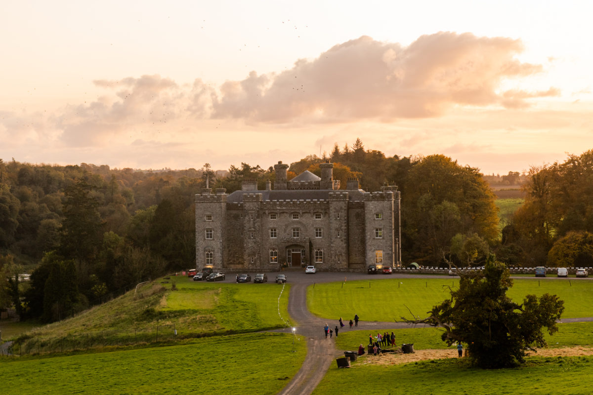 a large castle in the middle of a green field at sunset