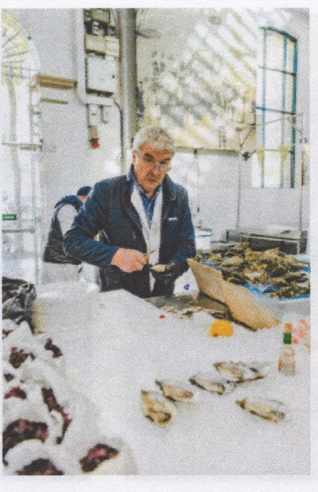 a man cuts into a fish at a market stand selling fish and oysters
