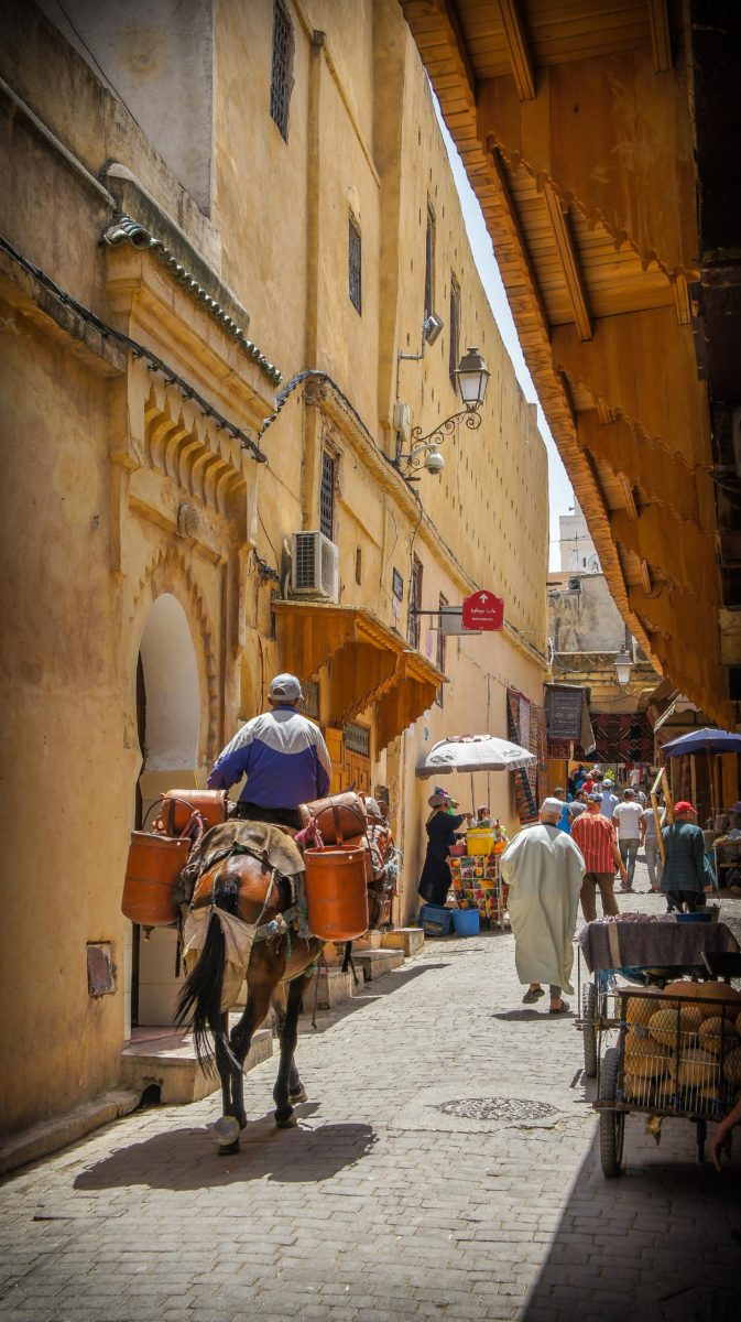 a man rides a camel carrying goods through a narrow marketplace alley