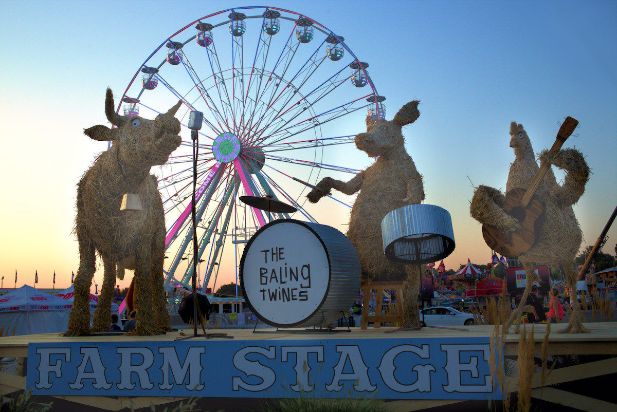 animals made of straw planing in a band in front of a ferris wheel