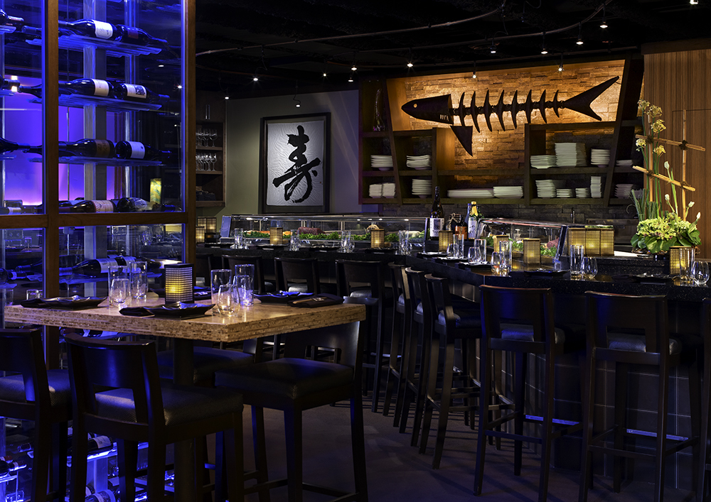 high tables, chairs, and a bar at a dimly lit Japanese restaurant