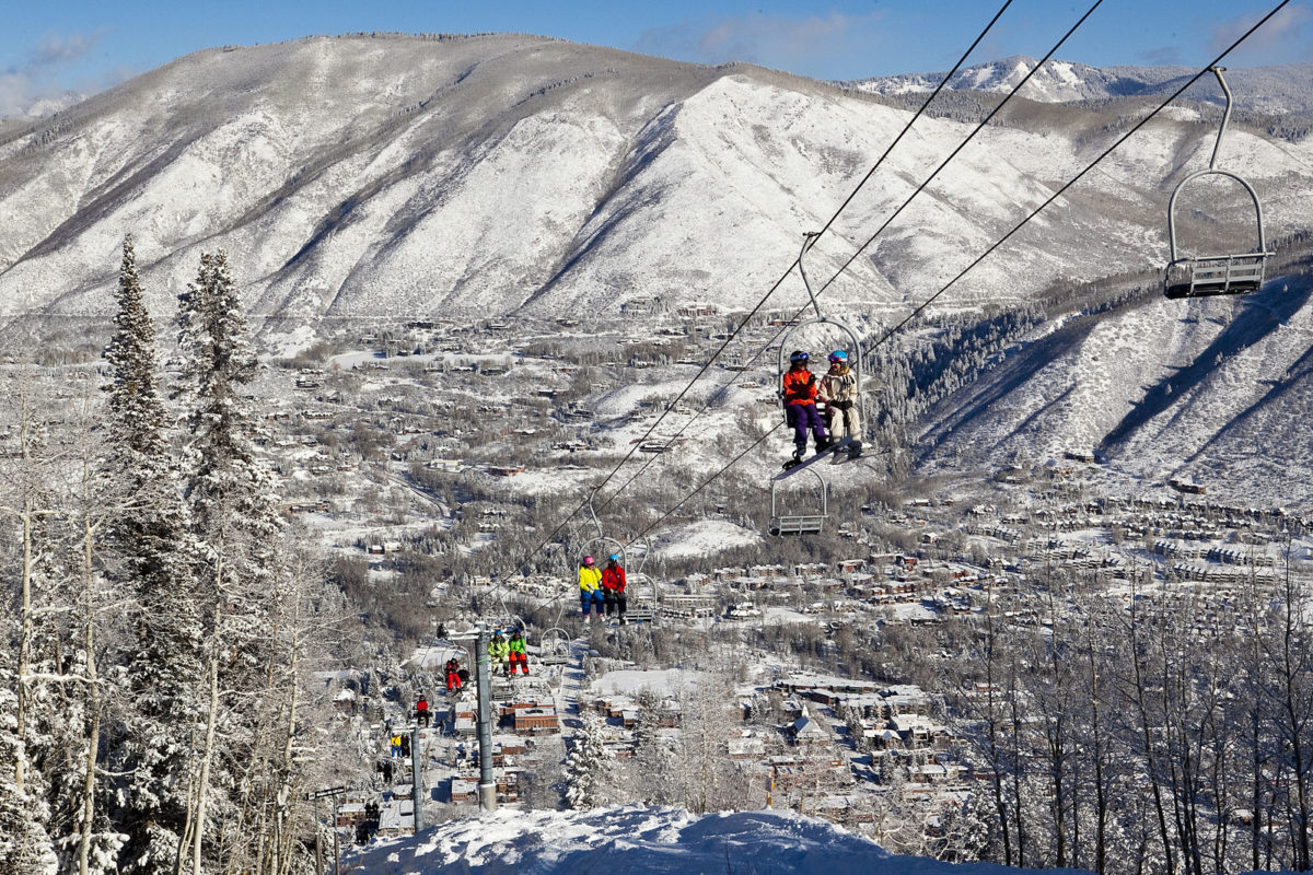 people going up in a ski lift with a mountain in the background on a snowy, sunny day