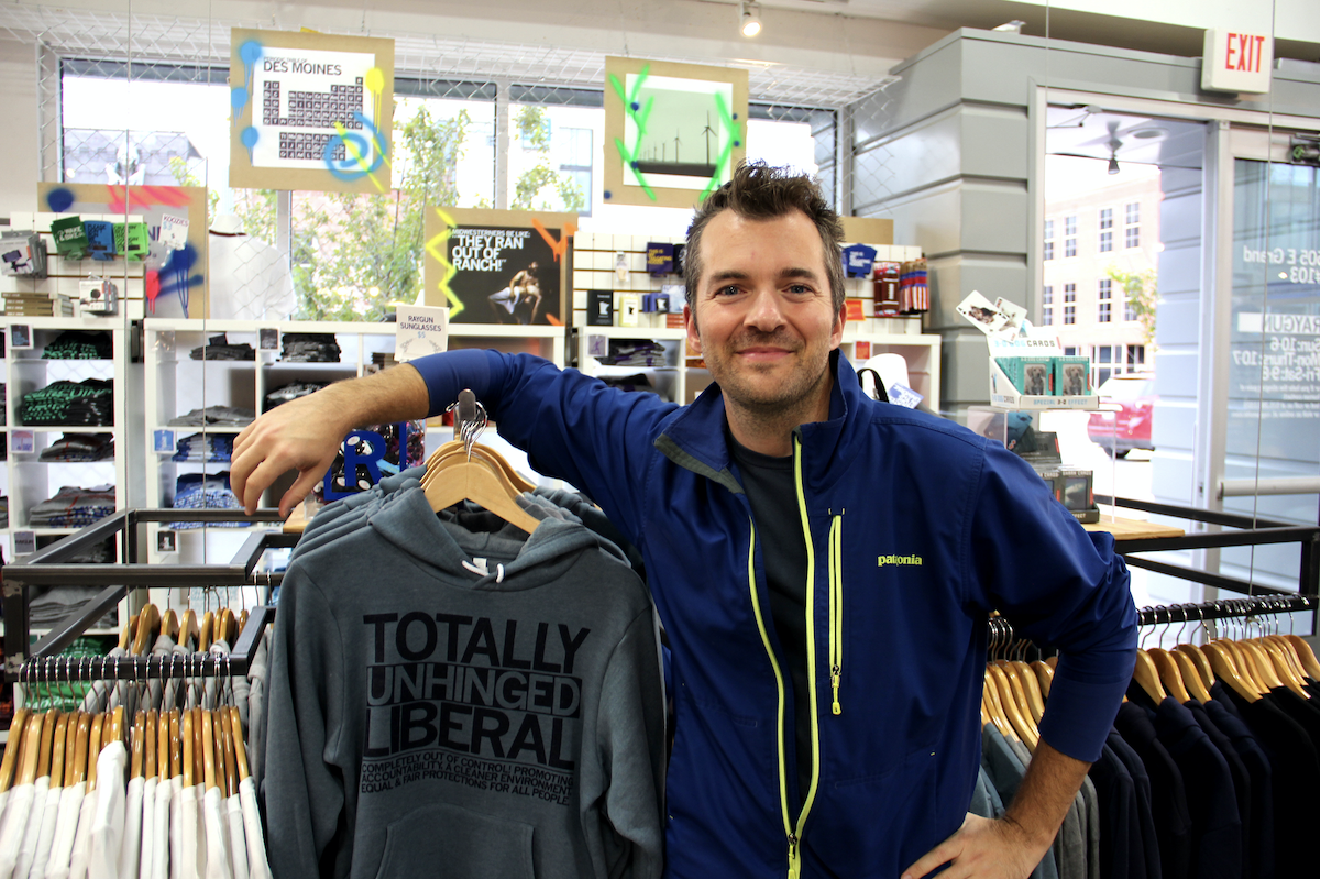 Mike Draper in his store next to racks of screenprinted shirts