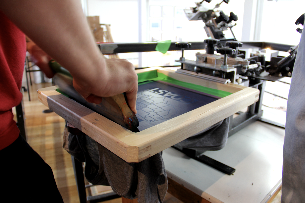 man screenprinting a shirt