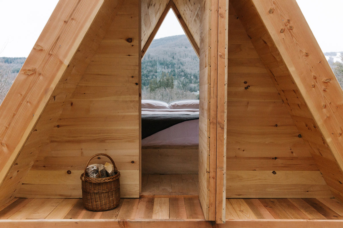 a wooden tent with a bed overlooking hills