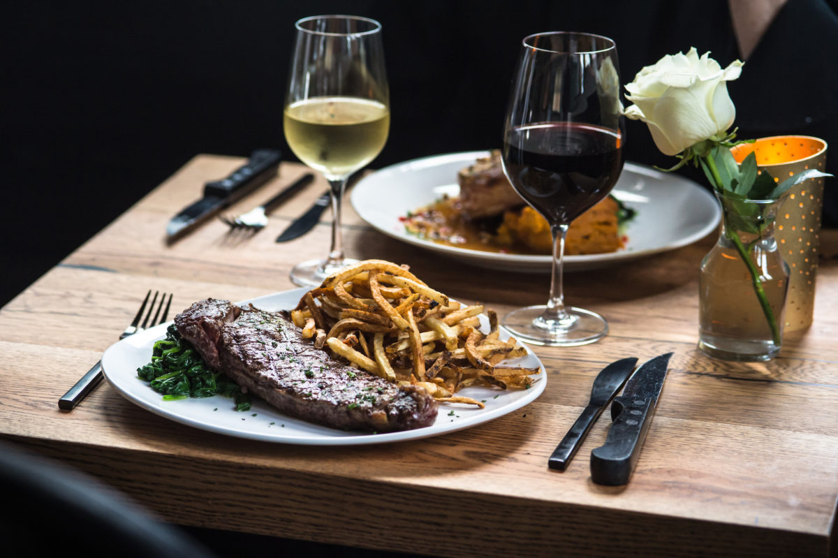 steak, fries, and wine on a table