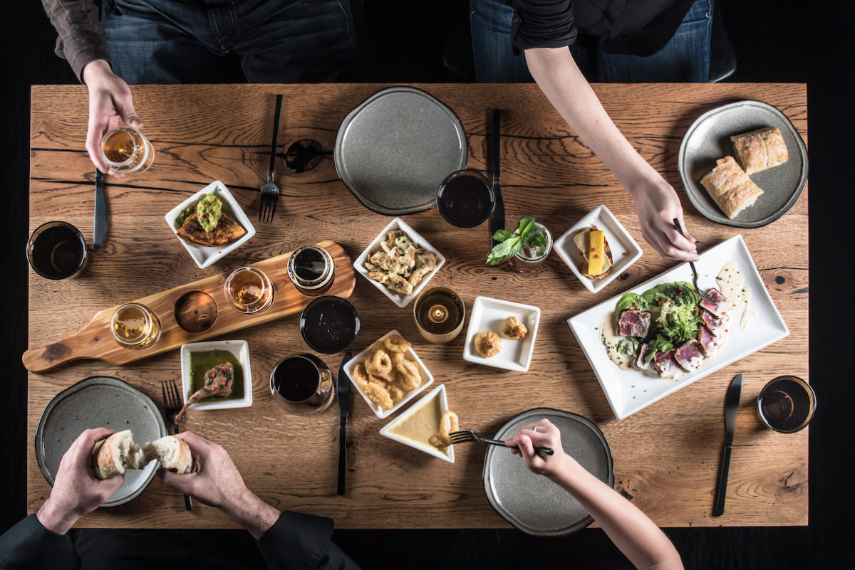 people reaching out towards plates on a table full of food