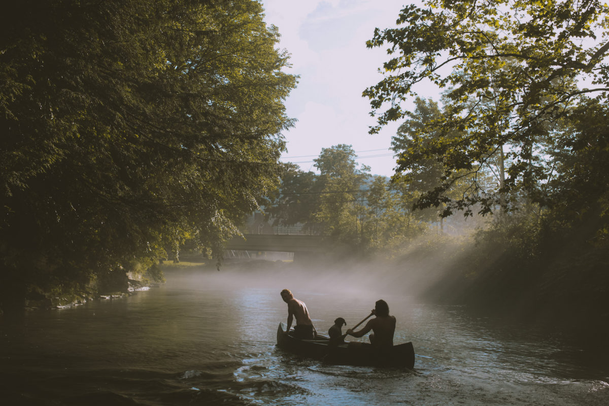 people rowing a canoe down a misty river