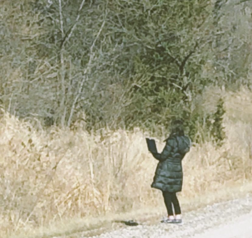 katie gluek reporting with her computer on the side of the road
