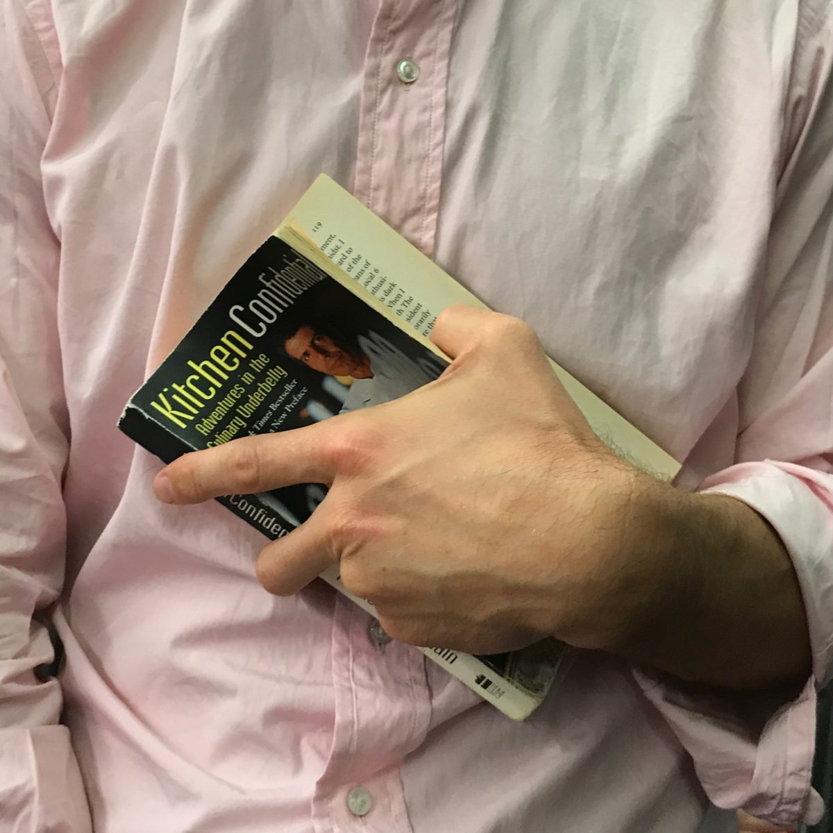a person's hand holding a book against their chest
