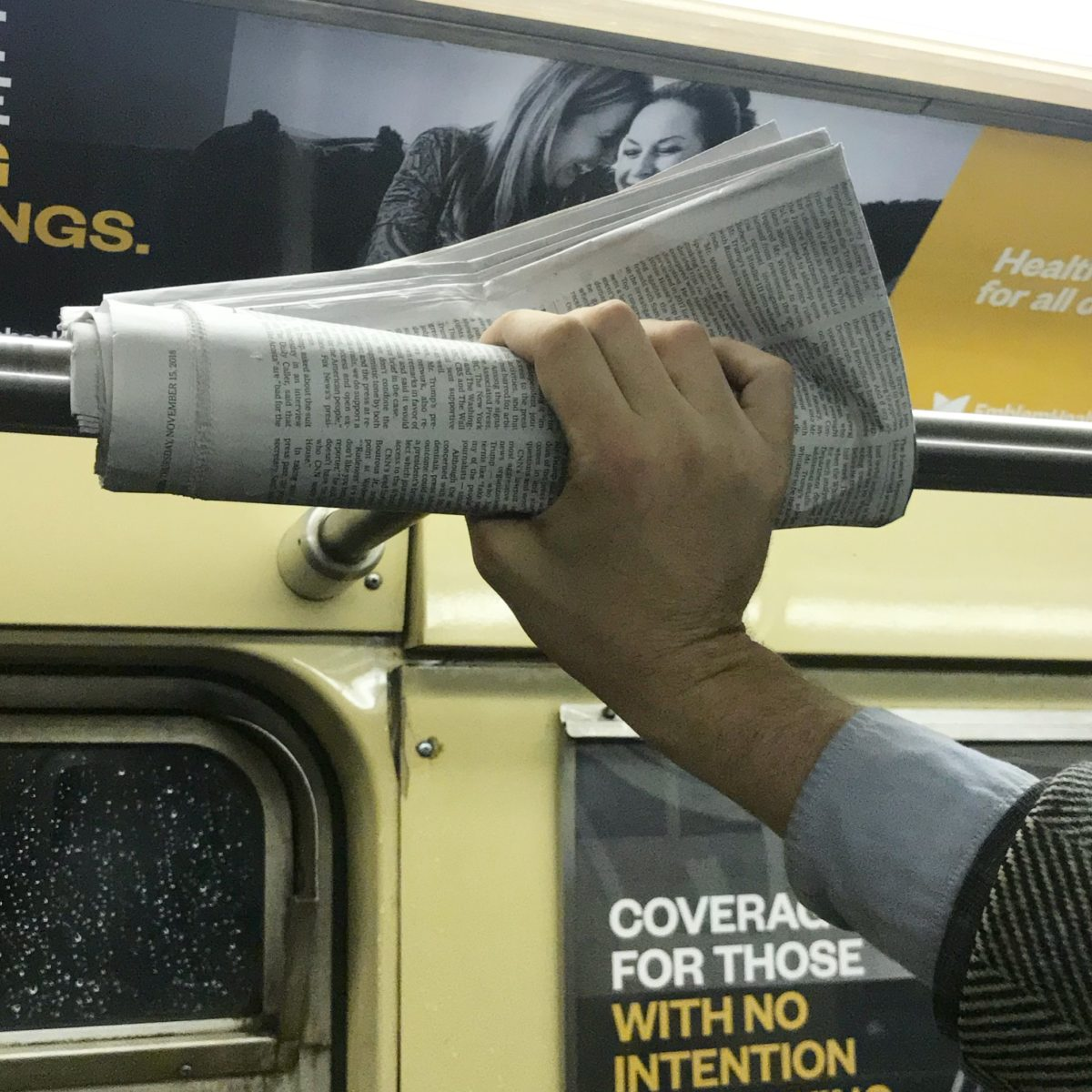 hand holding a newspaper against a subway rail