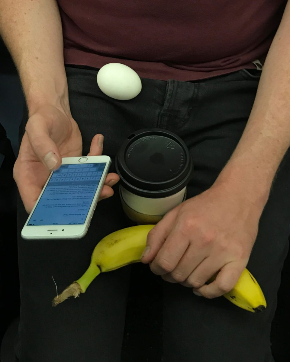 hands balancing a banana, phone, coffee, and egg