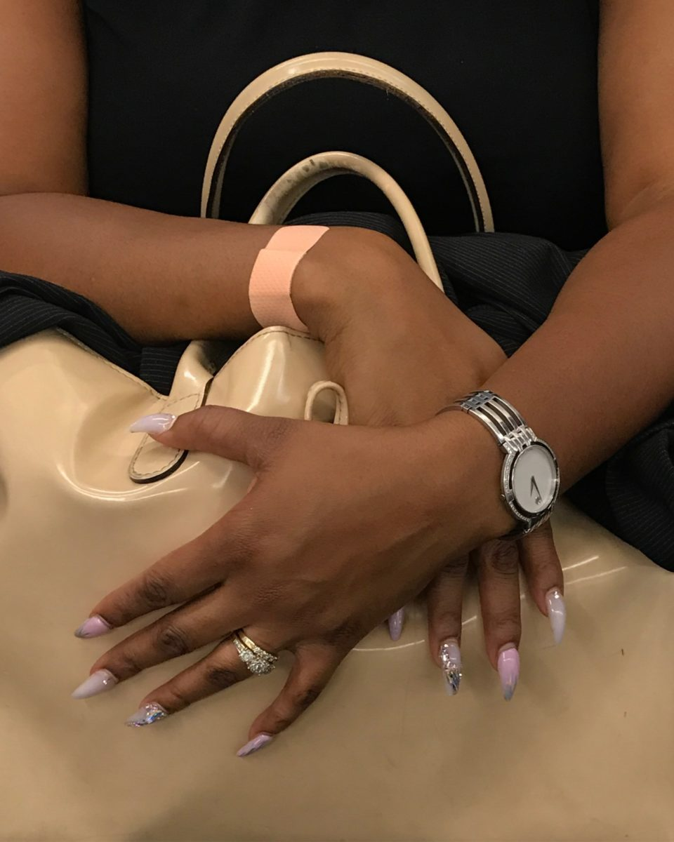hands with long decorative nails grasping a purse