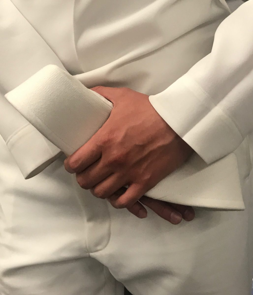 person in a button up with crossed hands