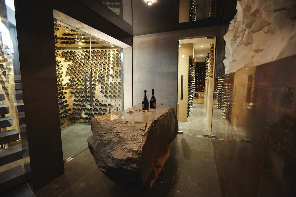 a hallway decorated with a giant stone leading to a wine room