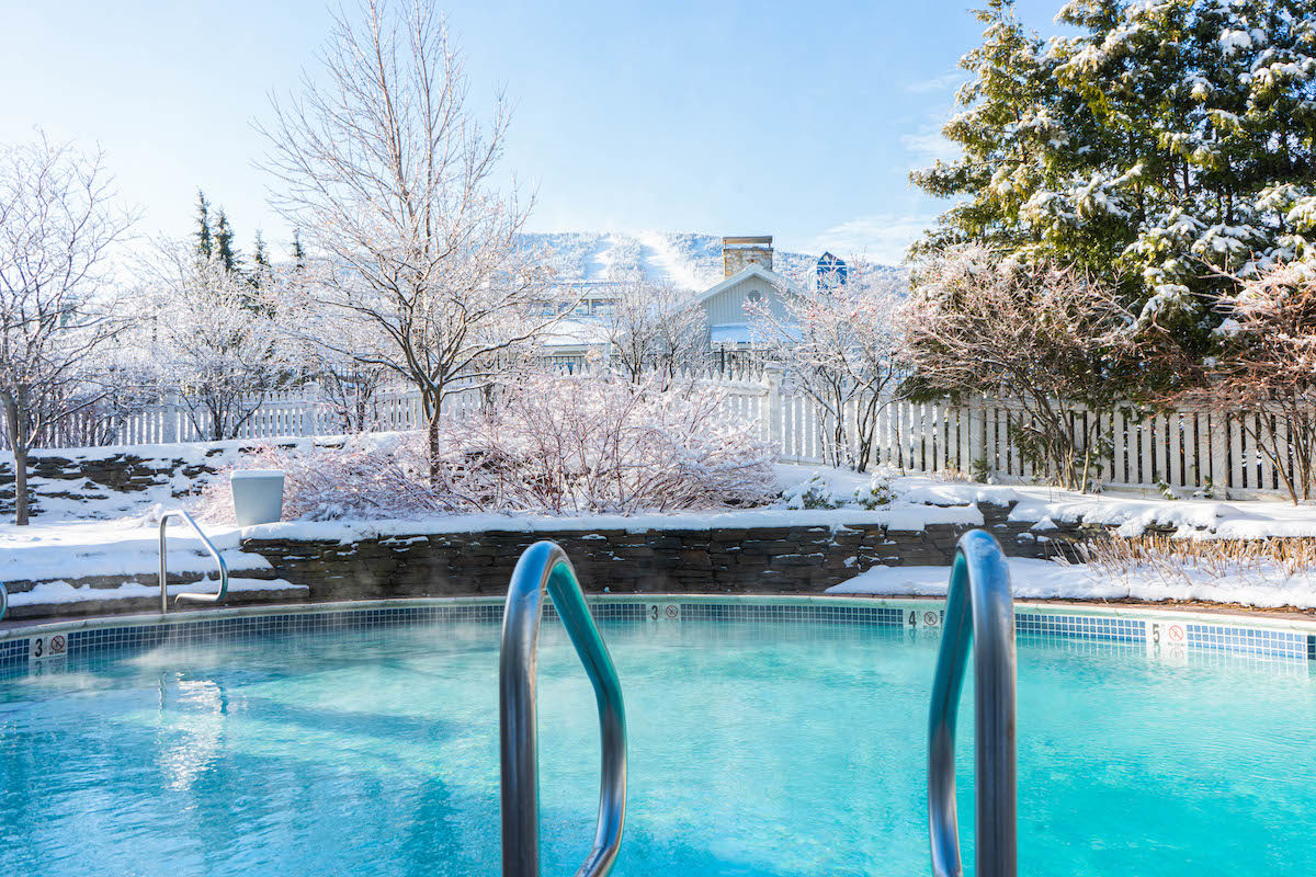 chlorine pool overlooking a snowy mountain peak through the trees
