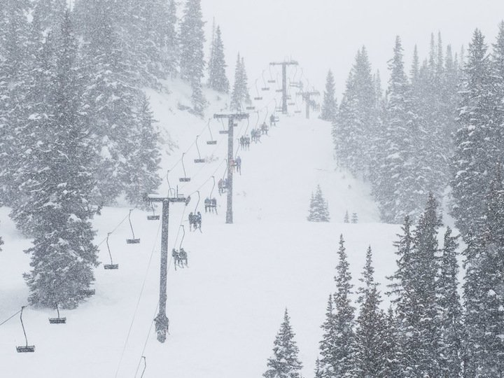 aerial view of ski lifts going up mountain obscured by snowy conditions