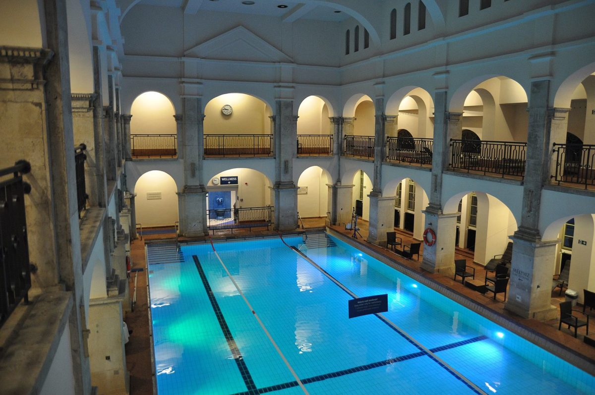an indoor public bath with columns at night