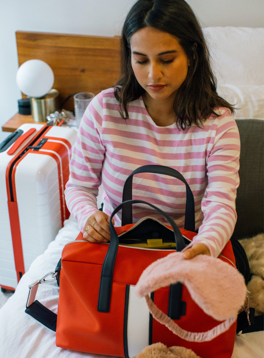 A woman packing a red Away Everywhere Bag from the Chalet Collection.