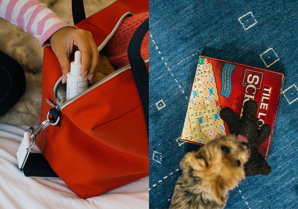 a woman packs a face serum into a red Everywhere Bag from Away's Chalet Collection. A dog sniffs a Scrabble board game box.