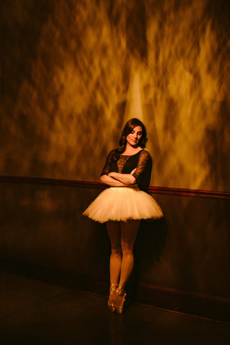 a ballerina leaning against a wall